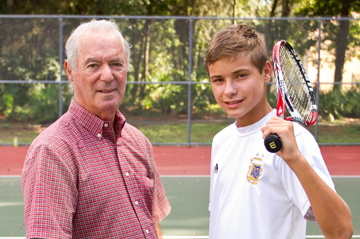 senior man and youth on tennis court