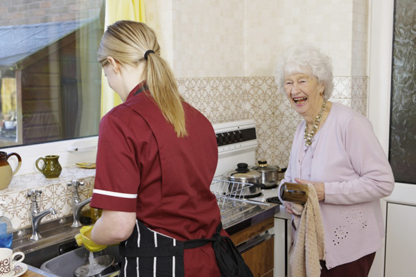 elderly woman assisted by homemaker in household chores