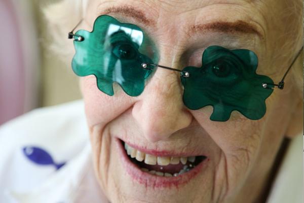 smiling senior woman with shamrock glasses