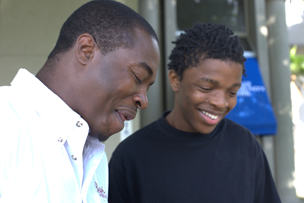Father and teen son talking and smiling