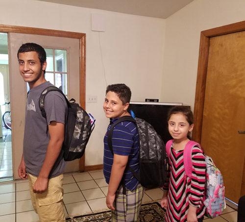 siblings show off new backpacks