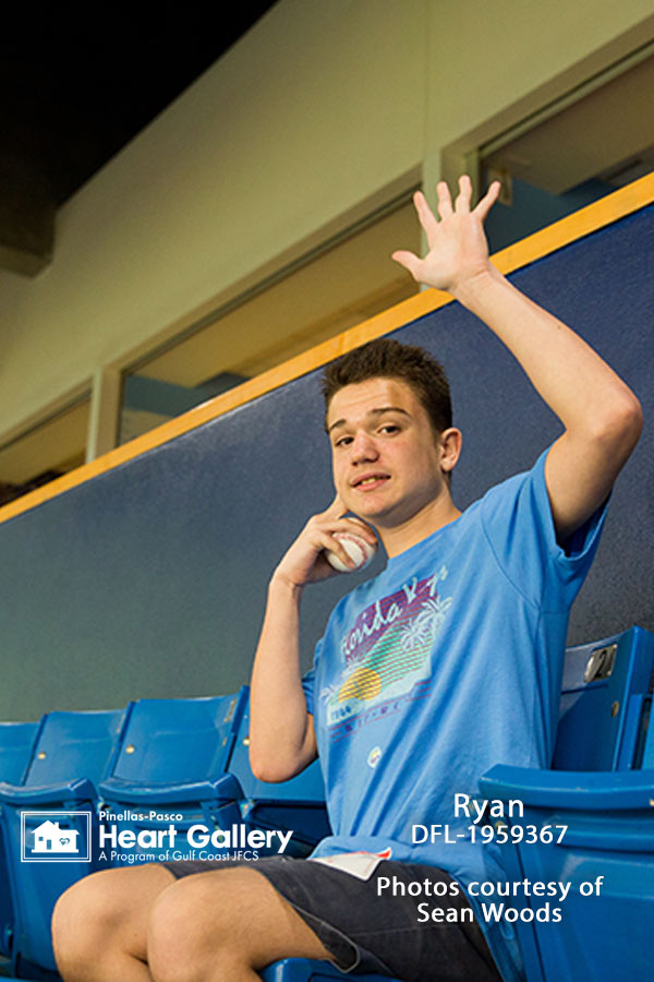 A boy with a blue shirt with a baseball