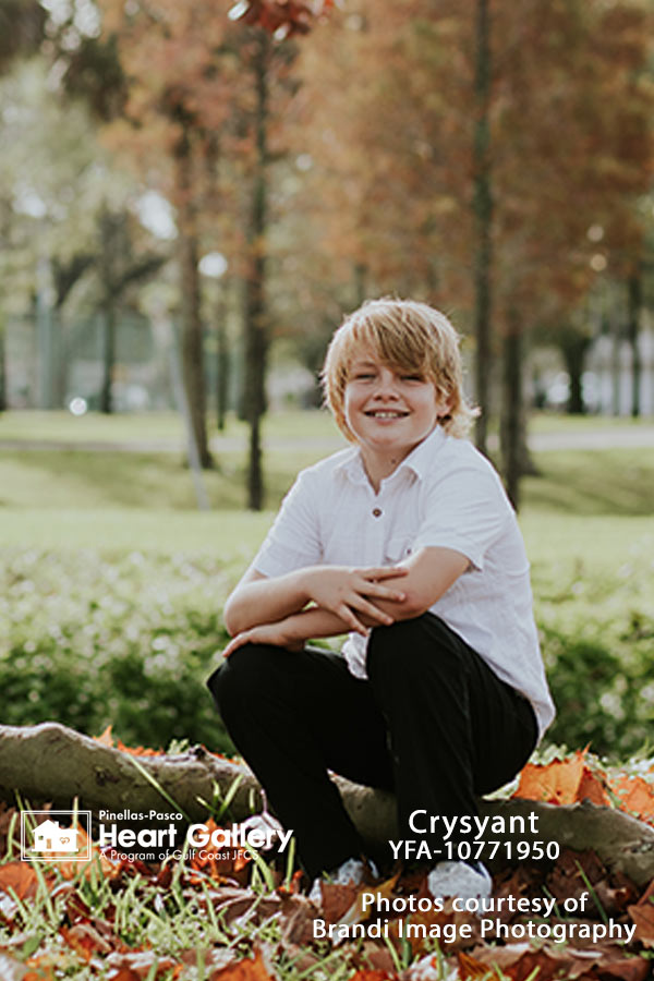 A boy with a white shirt in front of greenery