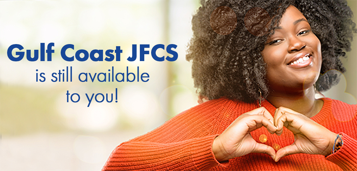 "Photo of smiling woman making heart sign, ""Gulf Coast JFCS is still available to you!"""