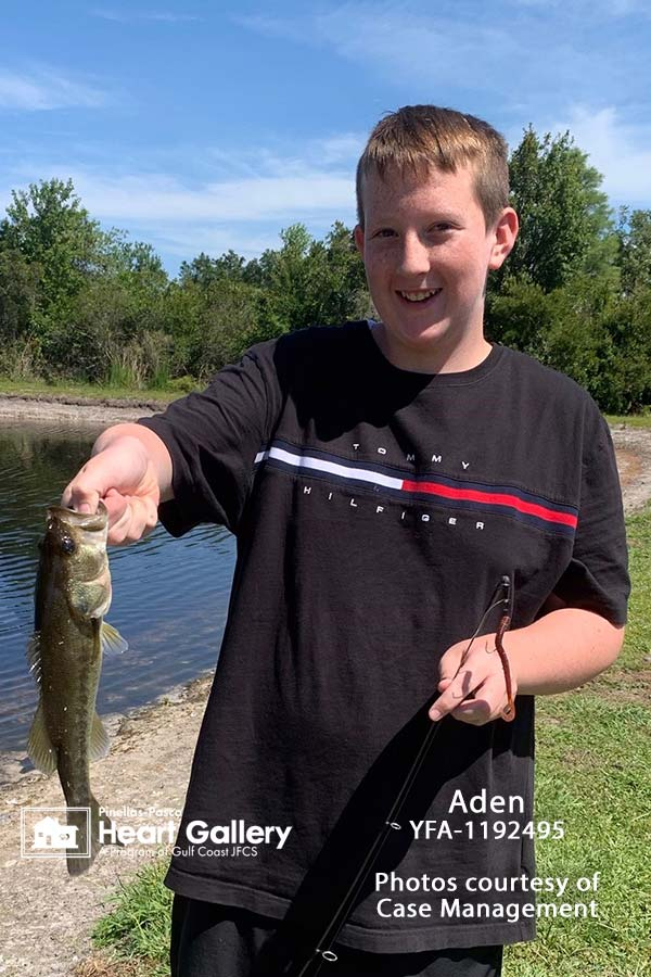A boy with a black shirt in front of a lake with a fish
