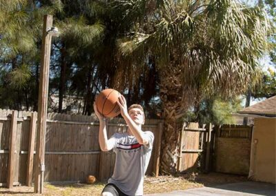 A boy with a grey shirt in front of a neighborhood with a basketball