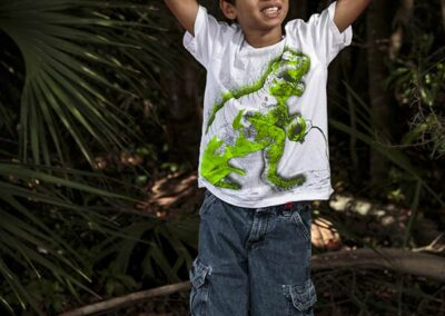 A boy with a white and green shirt in front of greenery