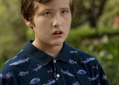 A boy with a fish shirt in front of greenery