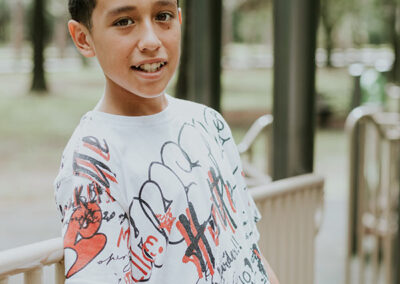 A boy with a graffiti shirt in front of a playground
